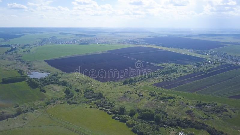 Aerial drone view of ploughed and green fields, trees, small town with blue cloudy sky on the background, agriculture stock image
