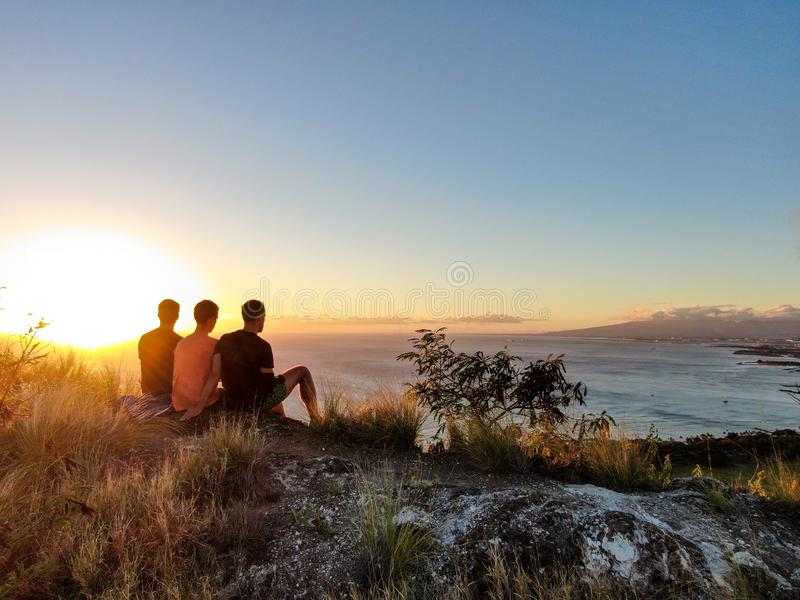 Aerial drone view of three young male hikers enjoying the sunset view on the summit of Diamond Head Crater royalty free stock photos