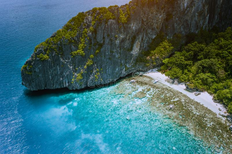 Aerial drone view of tropical beach with banca boats on Entalula Island. Karst limestone rocky mountains surrouns blue. Bay with beautiful coral reef stock photography