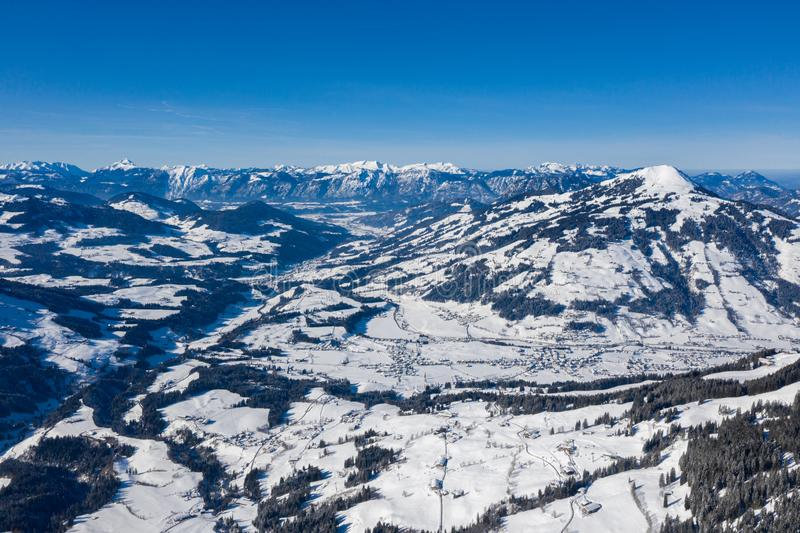 Aerial drone view of valley covered in snow in between mountains stock images