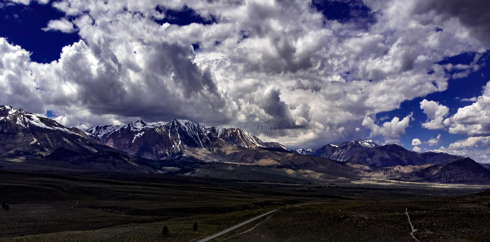 Aerial, drone view of white clouds over snow capped Eastern Sierra Nevada Mountains stock photos