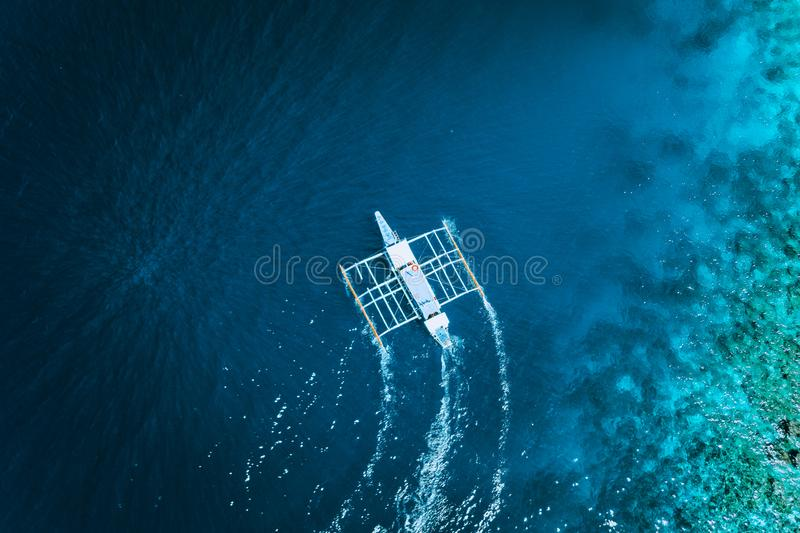 Aerial drone view of white traditional Filipino boat floating on top of clear blue water surface. El Nido, Palawan stock photography