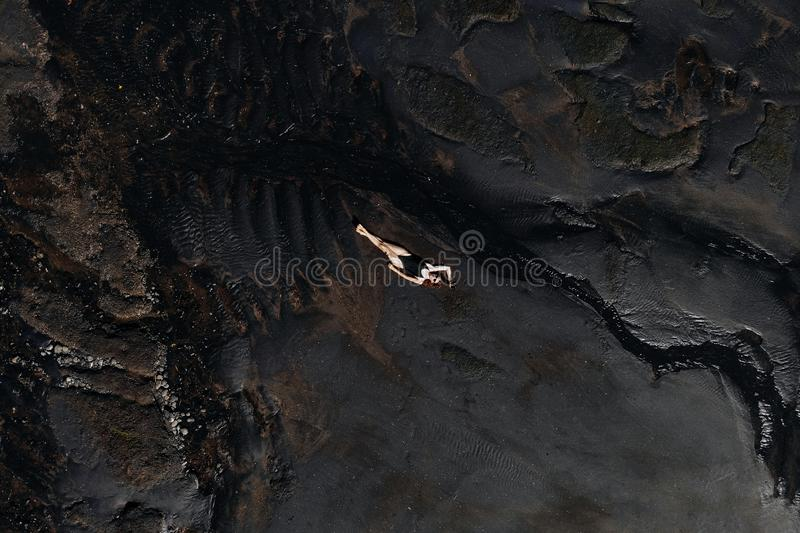 Aerial drone view of woman in black swimsuit lying relaxing on black sand beach. Bali Island, Indonesia.  stock photography