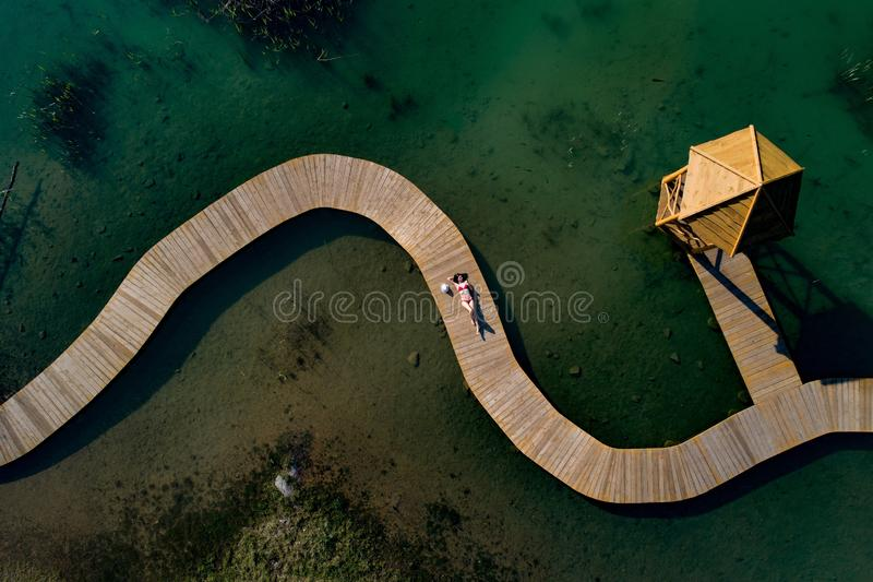 Aerial drone view woman in swimsuit sunbathing on the pier royalty free stock image