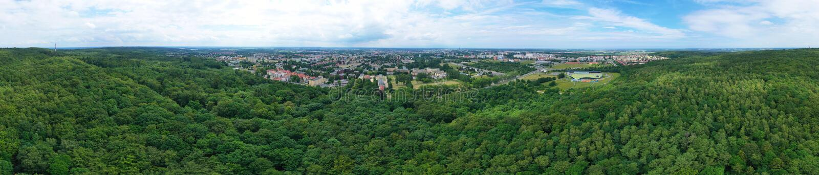 Aerial drone wide panoramic view on green lungs forest surrounding european city during summer, aquapark complex royalty free stock images