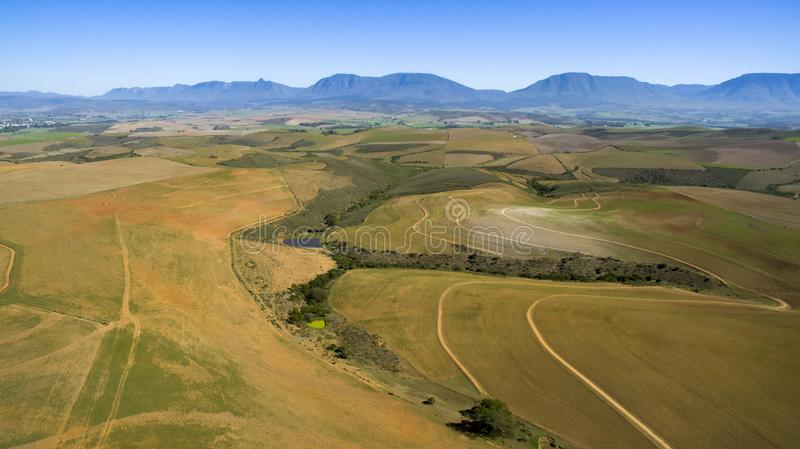 Aerial of farmland and mountains in South Africa. A valley surrounded by farmland in South Africa. This quiet little valley is a beautiful peaceful place in the stock image