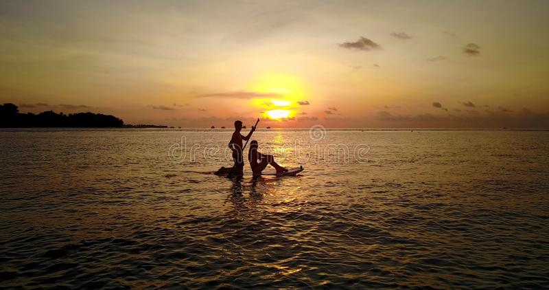 P00091 Aerial flying drone view of Maldives white sandy beach 2 people young couple man woman paddleboard rowing sunset. Aerial flying drone view of Maldives stock image