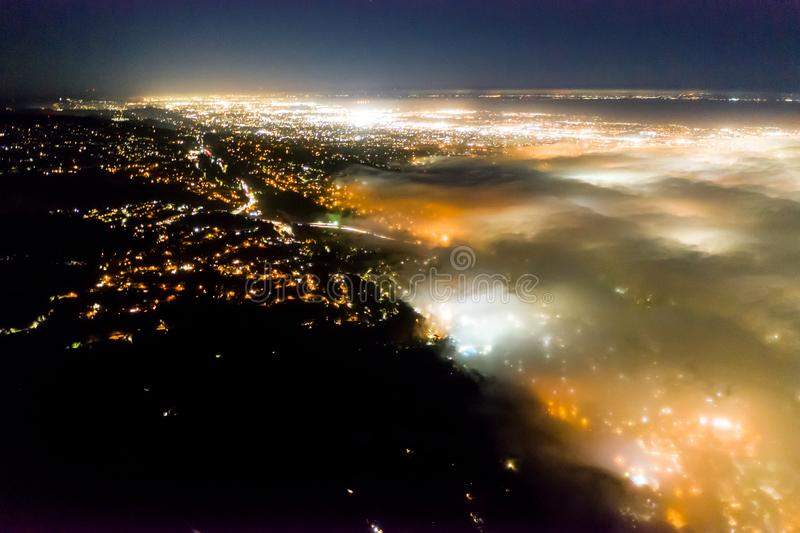 Aerial of Fog Flowing Into Bay Area, California, at Night. At night the ever-present offshore marine layer in California is propelled inland in the San Francisco stock photo