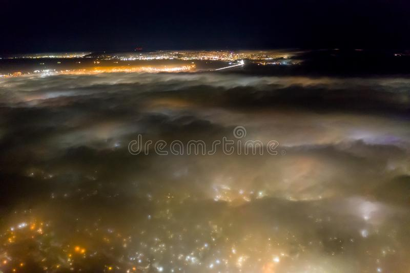 Aerial of Fog Flowing Over Bay Area, California, at Night. At night the ever-present offshore marine layer in California is propelled inland in the San Francisco royalty free stock photos