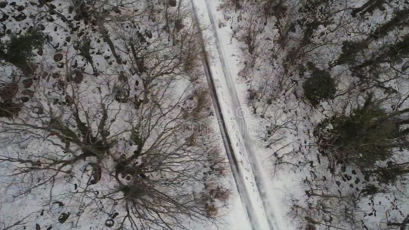 Aerial for the forest covered with snow and winter road, bird eye view. Shot. Top view of country road going through the stock photos