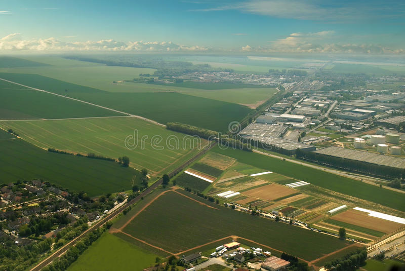 Aerial of green countryside & industrial city. Bird's eye view of beautiful colorful French village countryside, industrial city. Saving nature industry .Sky royalty free stock photo