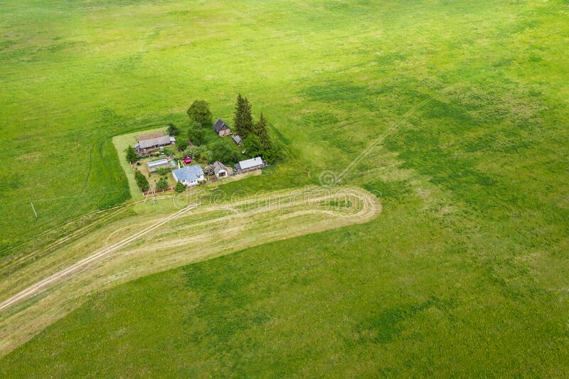 Aerial landscape with farm house, equipment and warehouses among green fields stock photos