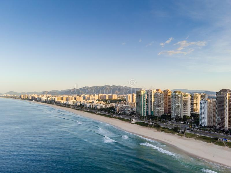 Aerial landscape photo of Barra da Tijuca beach , with waves crashing on beach during sunrise, with the beachfront stock image