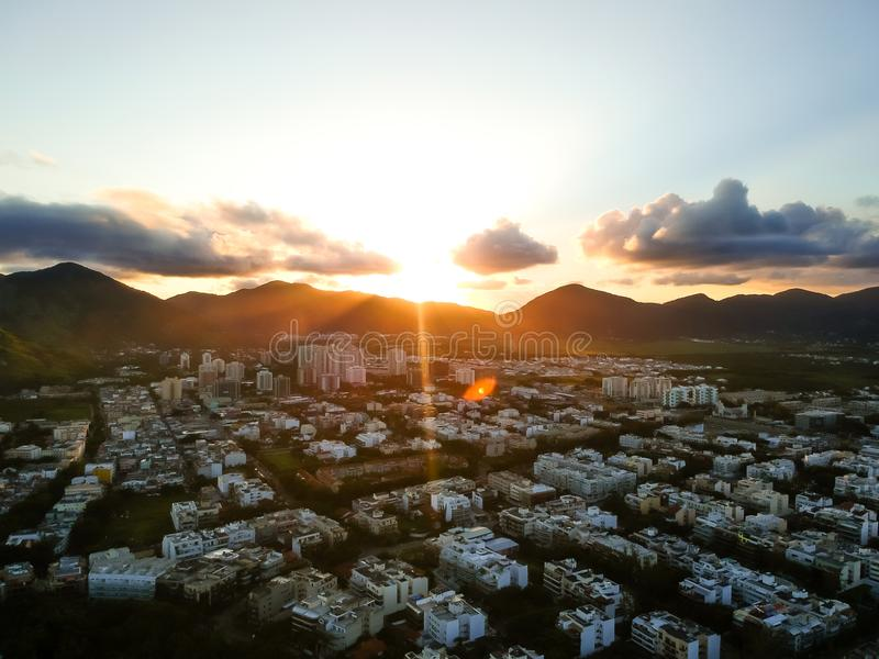 Aerial landscape photo of Recreio dos Bandeirantes beach during sunset, with the sun dipping behind the mountains and royalty free stock photo