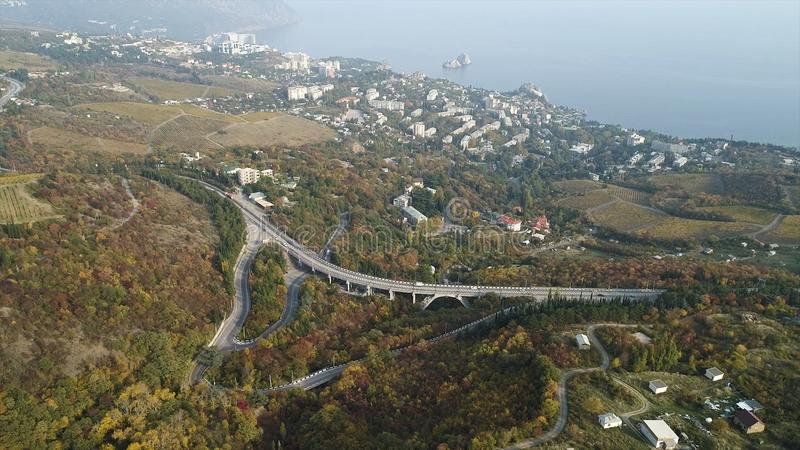 Aerial landscape view of a beautiful bay with forest and hills, small town, and motorway. Shot. Beautiful foggy scenery royalty free stock photos