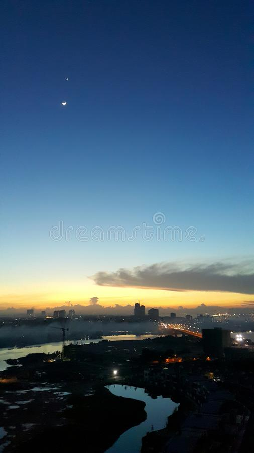 Aerial landscape view of cityscape while dawn breaking with beautiful hues with star and moon still in sight stock photo