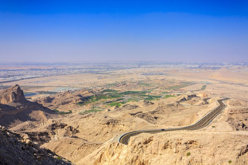 Aerial view on twisty mountain road, Jebel Hafeet park and Al Ain city in UAE royalty free stock photo
