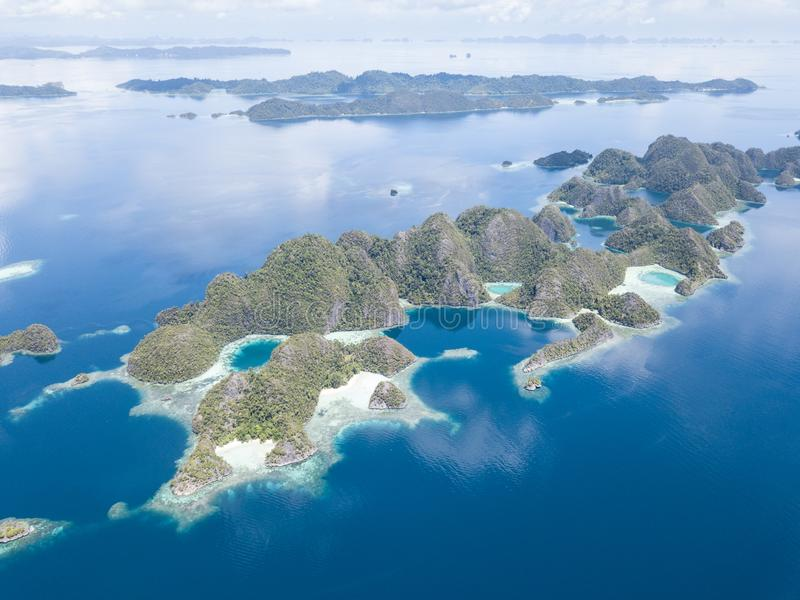 Aerial of Limestone Islands in Raja Ampat. The limestone islands found in Raja Ampat rise from calm, blue seas in a remote part of eastern Indonesia. This royalty free stock image