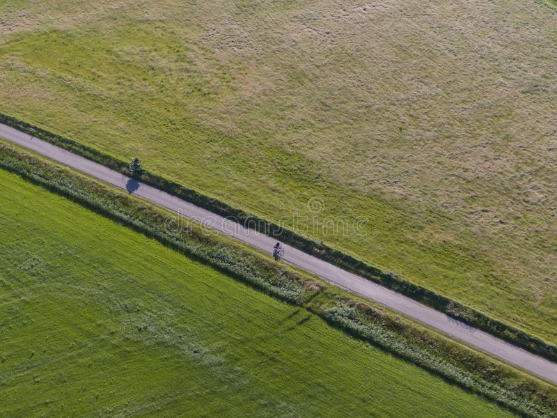 Aerial of meadowland separated by straight bicycle lane with cyclist on the dutch island of Texel royalty free stock photos