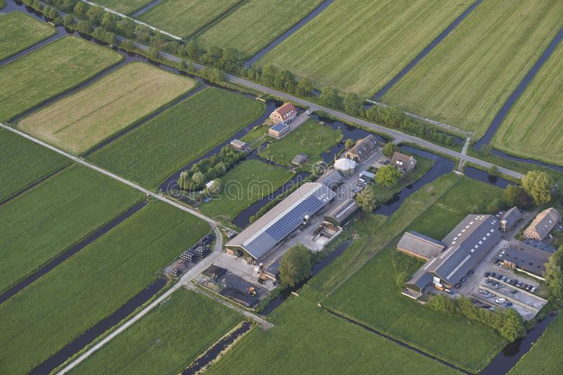 Aerial of modern farms with solar panels on the roof in dutch meadow landscape royalty free stock photography
