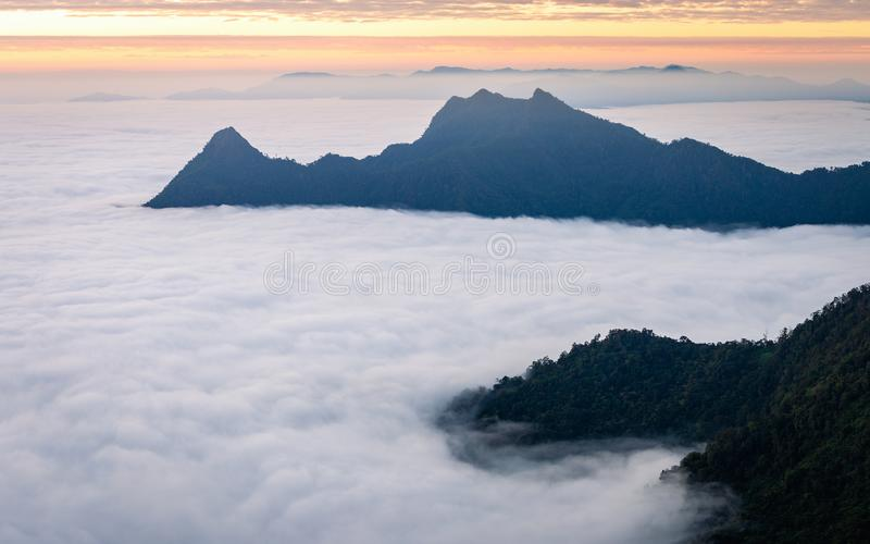 Fog cover dark mountain in Chiangrai, Thailand. Aerial morning view of white fog cover all area of mountain and hill of Phu Chi Fa tropical forest in Chiangrai stock images