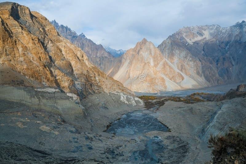 Mountain peaks in Karakoram range near moraine and glacial lake in Passu stock photography