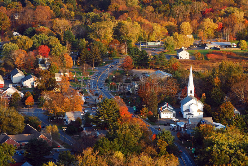 Aerial of a New England village in Autumn. The colorful autumn leaves surround a charming New England village royalty free stock images