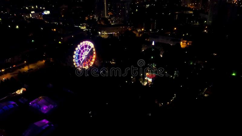 Aerial night view of city skyline and ferris wheel. Top view of Ferris Wheel in the central park at night. Clip. stock photography