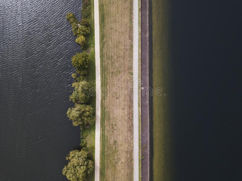 Aerial overhead shot of a brown road near the body of water at daytime. An aerial overhead shot of a brown road near the body of water at daytime royalty free stock images