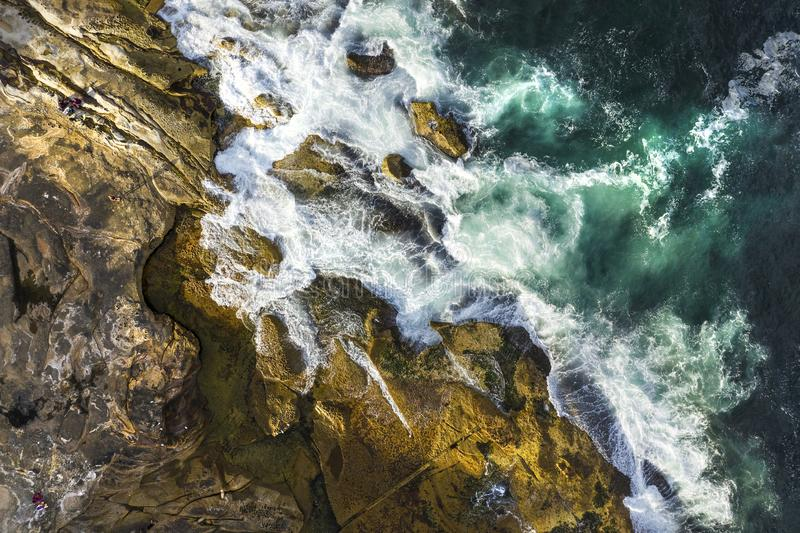 Aerial, overhead view of waves and a rocky shoreline. In Sydney, Australia royalty free stock photos