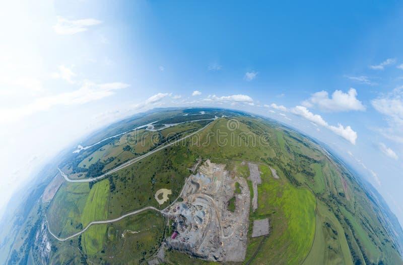 Aerial 360 panorâmico de minerais de pedreira a céu aberto com muitos tratores e caminhões de máquinas cercados por campos verdes imagem de stock