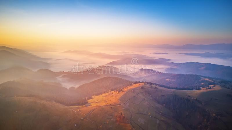 Aerial panorama of autumn mountains. Sunrise over foggy valley royalty free stock images