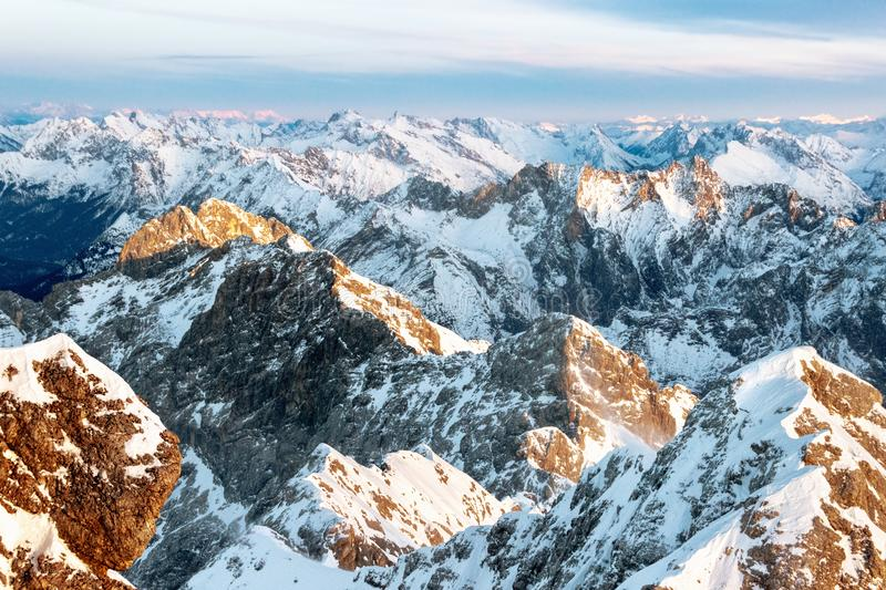 Brown and white snowy mountain tops in sunset. Aerial panorama of brown and white snow-covered mountain summits under the cloudy sky till horizon stock photos