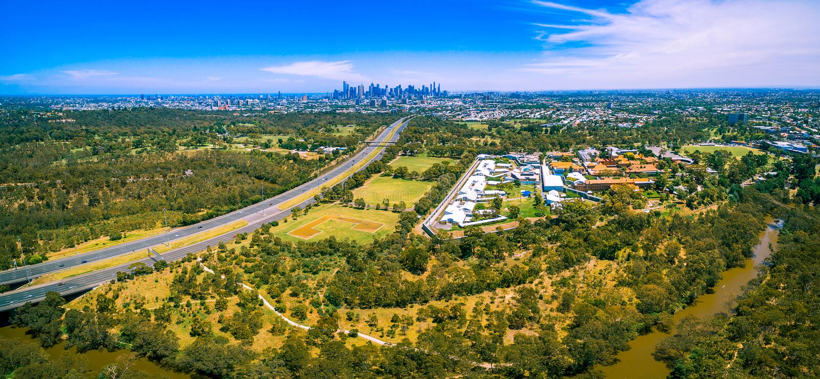 Aerial panorama of Eastern Freeway and Melbourne CBD skyscrapers on bright summer day. stock image