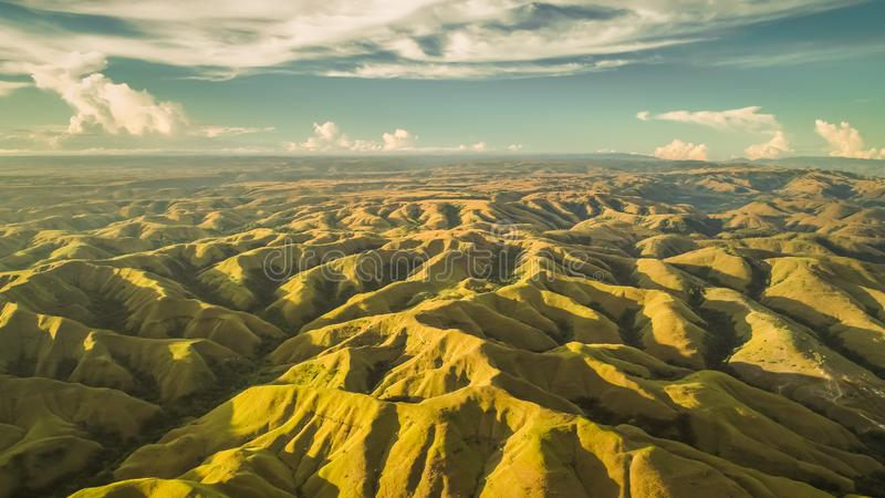 Aerial panorama green hills. Drone shot. Indonesia. Breathtaking landscape hilly surface on the blue cloudy sky background. Sumba island. Magnificient beauty royalty free stock photos