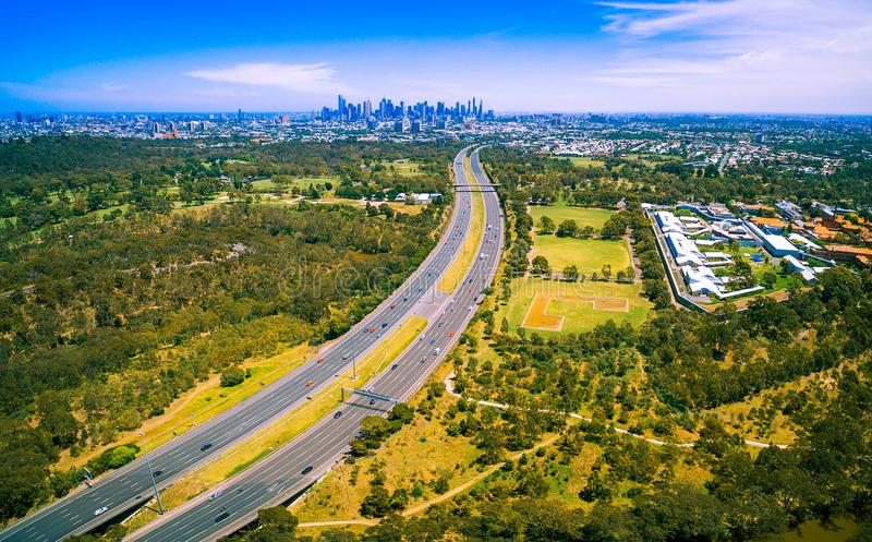 Aerial panorama of green parkland, Melbourne Polytechnic, and Melbourne CBD skyscrapers in the distance on summer day. royalty free stock photo