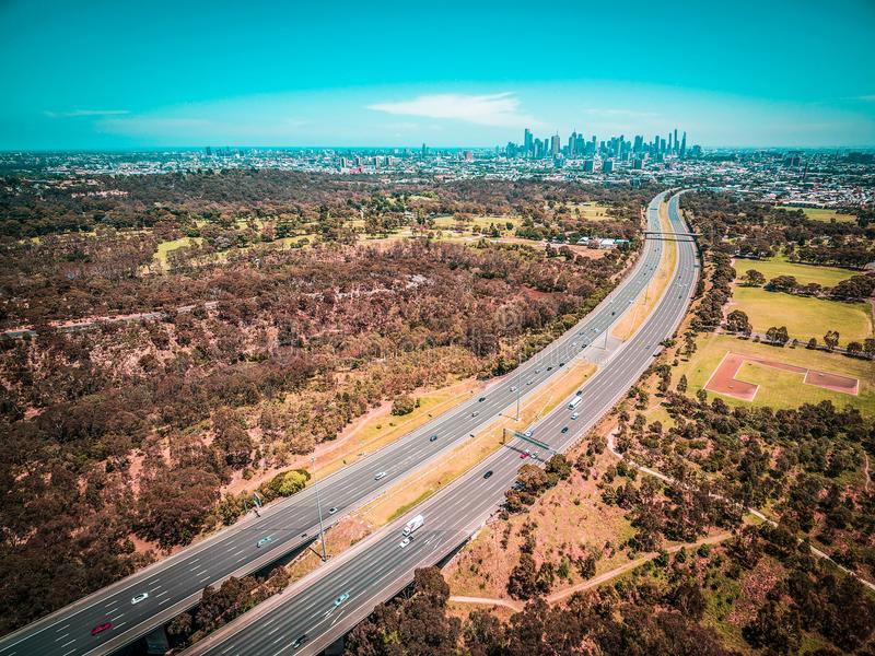 Aerial panorama of highway leading to Melbourne downtown skyscrapers on hot summer day. stock photography