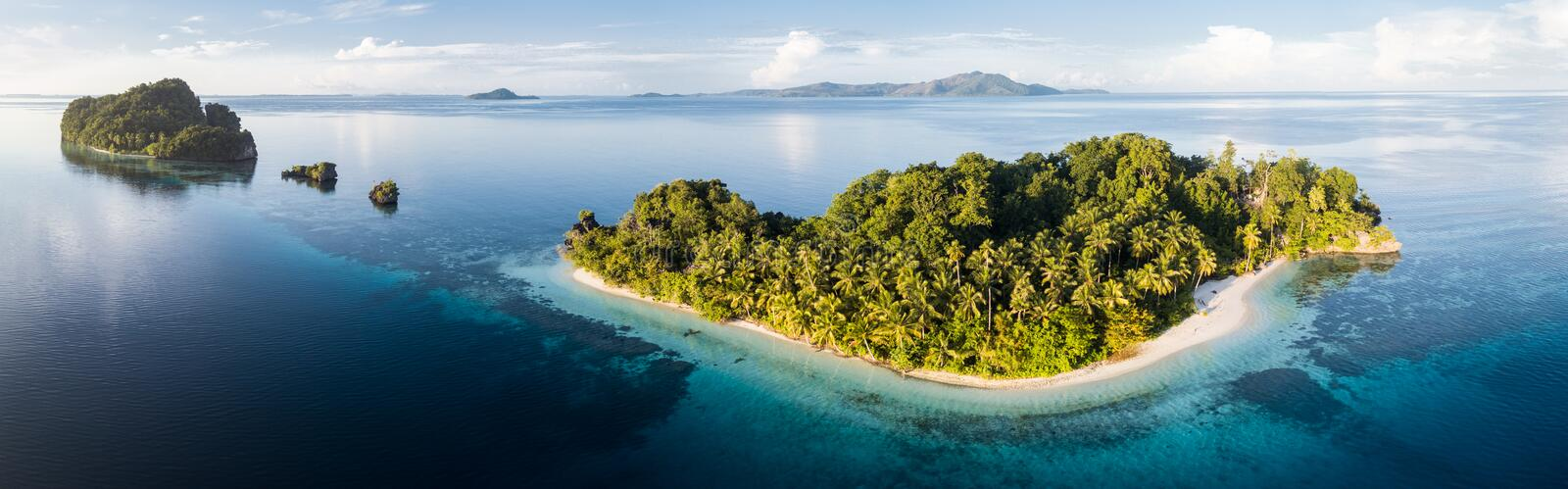 Aerial Panorama of Idyllic, Tropical Islands in Raja Ampat. The islands found throughout Raja Ampat, Indonesia, are surrounded by flourishing coral reefs and stock photography