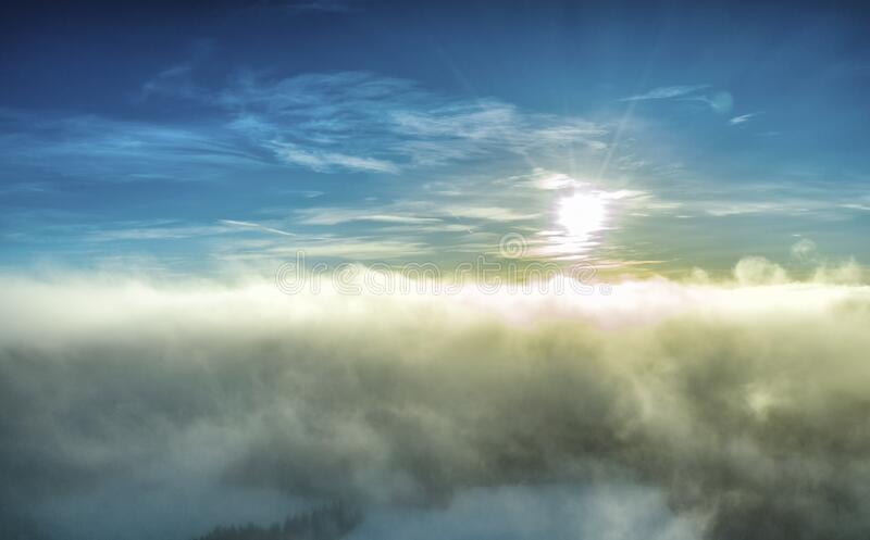 Aerial panorama photo of winter Sun before sunset above frosty subarctic clouds, very fluffy light clouds colored by sun rays and. Darkened from below by frosty royalty free stock photography