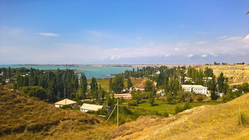 Aerial panorama view to Karakol towm, formerly Przhevalsk, and Issyk-Kul lake, Kyrgyzstan royalty free stock photos