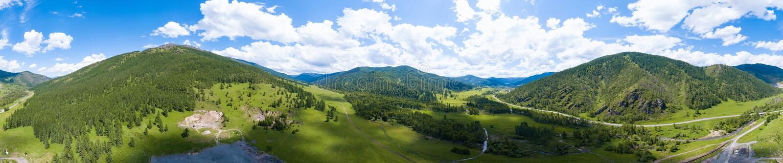 Panoramic banner view of landscape with mountains, green trees, field, road and river under blue sky and clouds in summer. Aerial panoramic banner view of stock photos