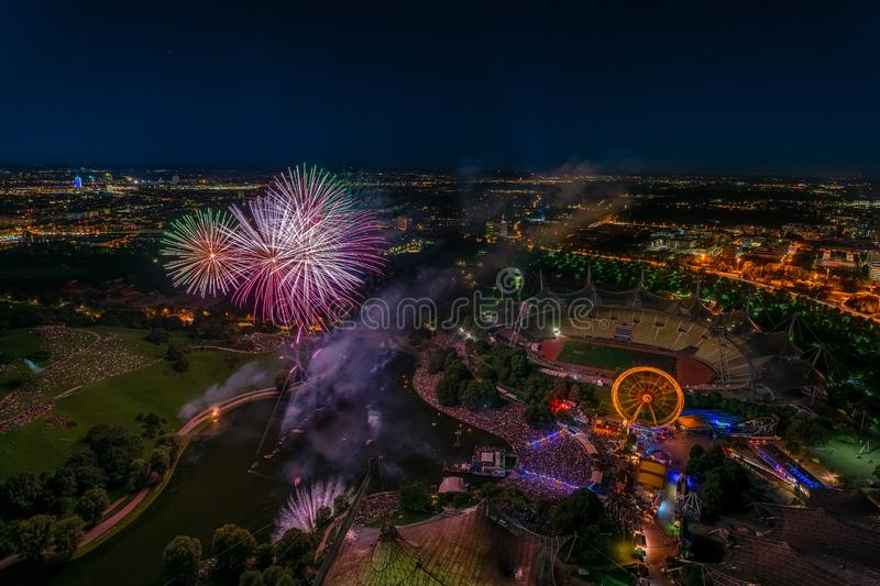 Aerial panoramic cityscape view with bright fireworks lights in night Munich. stock images