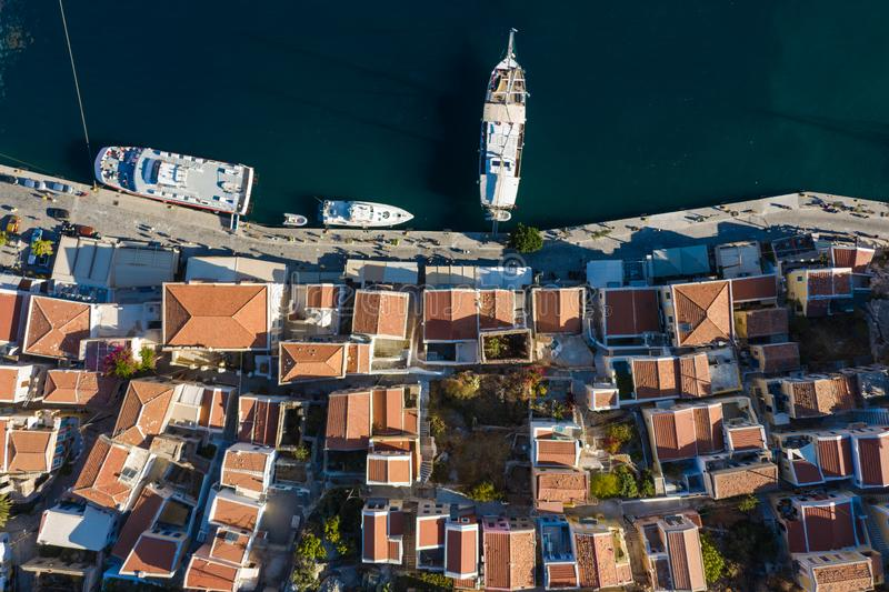 Aerial panoramic view on beautiful Greek houses on island hills, yacht sea port, tourist ferry boat at Aegean Sea bay. Greece. Panoramic view on beautiful Greek royalty free stock images