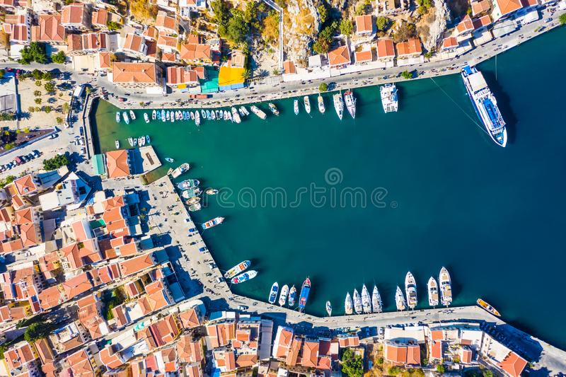 Aerial panoramic view on beautiful Greek houses on island hills, yacht sea port, tourist ferry boat at Aegean Sea bay. Greece. Panoramic view on beautiful Greek stock image