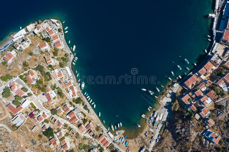 Aerial panoramic view on beautiful Greek houses on island hills, yacht sea port, tourist ferry boat at Aegean Sea bay. Greece. Panoramic view on beautiful Greek royalty free stock photography