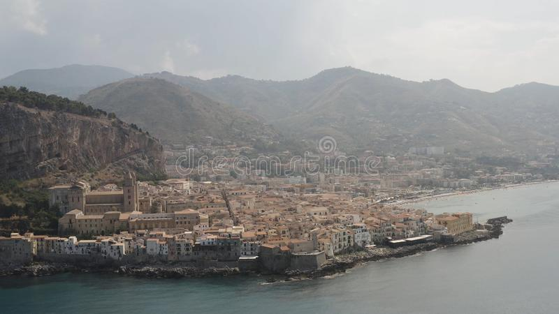 Aerial panoramic view of a coastal town near the mountains on cloudy sky background. Action. Beautiful landscape of the stock photography