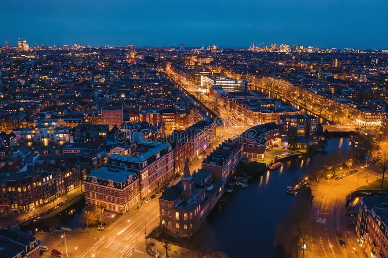 Aerial panoramic view of evening Amsterdam with water canals, illuminated roads and historic buildings, The Netherlands.  royalty free stock photos