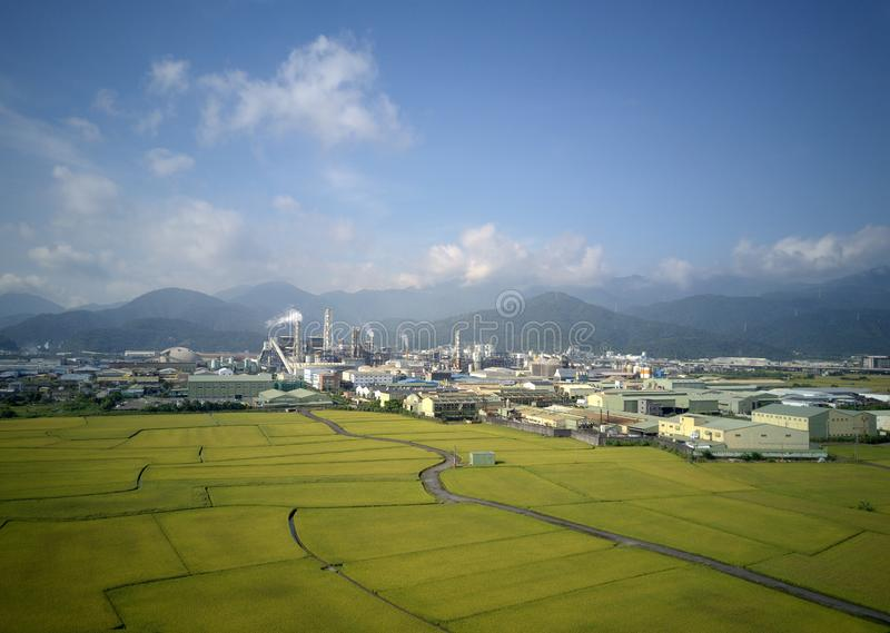 Aerial panoramic view of a factory with smoking chimneys by green rice paddies in Yilan Ilan royalty free stock image