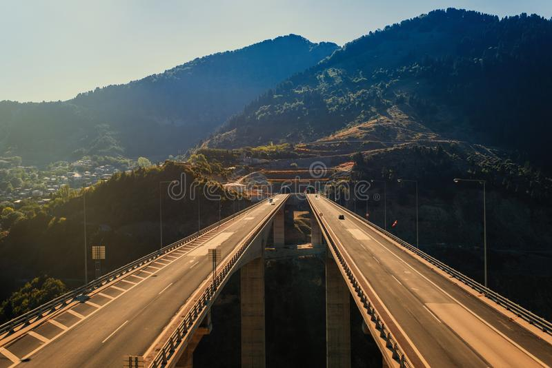 Aerial panoramic view on the highway bridge over the deep gorge royalty free stock photography