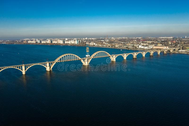 Aerial panoramic view on old arch railway Merefo-Kherson bridge across the Dnieper river in Dnepropetrovsk. View of the. Left bank of Dnipro city stock photo